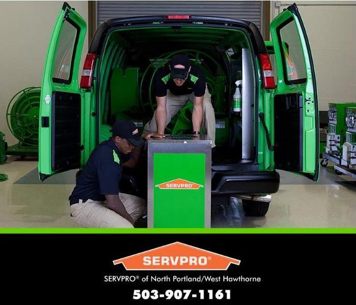 servpro technicians loading equipment into a van